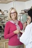 Stående av bärande exponeringsglas för hög kvinna medan optikerinnehavspegel Royaltyfri Foto