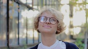 Stående av bärande exponeringsglas för lycklig blond kvinna och att se kameran och av ta exponeringsglas stock video