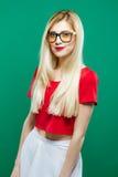 Stående av bärande glasögon för gullig flicka, kjol för röd överkant och vitpå grön bakgrund Ung kvinna med sinnliga kanter och Arkivbilder