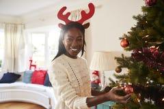 Stående av bärande horn på kronhjort för kvinna som hemma hänger garneringar på julgranen royaltyfri fotografi