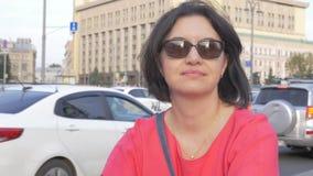 Stående av bärande solglasögon för en medelålders kvinna, som vilar i staden, mot bakgrunden av rörande bilar lager videofilmer