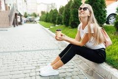 Stående av bärande solglasögon för en ung kvinna utomhus med coffe royaltyfri fotografi