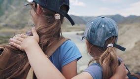 Stående av barn med ryggsäckar på bakgrunden av berg två små flickor fotvandrar i vandringen och tycker om sikten lager videofilmer