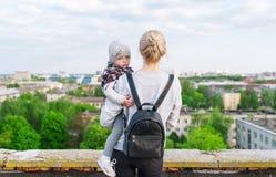 Stående av barn moder och dotterhandelsresande som står på stadstaket isolated rear view white Royaltyfri Bild