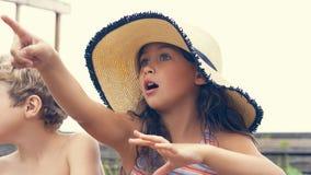 Stående av barn på stranden i sommar Liten flicka i en hatt som talar till hennes broder och le De sitter fotografering för bildbyråer