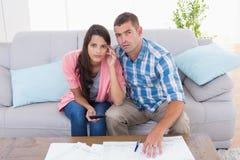 Stående av bekymrade par som hem beräknar finanser Arkivbild