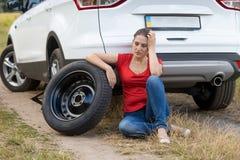 Stående av benägenheten för ung kvinna på bilen med det plana gummihjulet i fält Arkivbilder