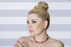 Stående av blondinen i hög grad på en blå bakgrund för två färg Royaltyfri Bild