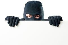 Stående av brottslingen i maskeringen med en stor affisch royaltyfri foto