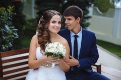 Stående av bruden och brudgummen som är le och krama lyckligt sammanträde i parkera Mannen kramar försiktigt hans fru arkivbild