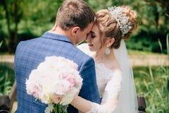 Stående av brudgummen som cirklar hans brud i trädgården på hans bröllopdag Vänner kyss och kram efter förbindelsen Arkivfoto