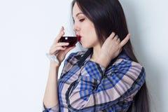 Stående av brunetten som slår hennes hår och dricker rött vin Royaltyfria Foton