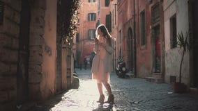 Stående av brunettkvinnaanseendet i den lilla gatan och att använda pekskärmteknologi på smartphonen Royaltyfri Bild