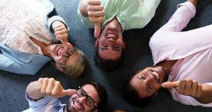 Stående av businesspeople som visar upp tummar, medan ligga på golvet stock video