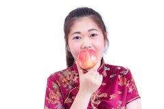 Stående av cheongsam eller qipaoen för härlig ung asiatisk klänning för kvinnakläder kinesisk traditionell Äta det röda äpplet, Royaltyfri Foto