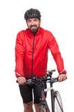 Stående av cyklisten med hjälmen och det röda omslaget som poserar bredvid en cykel som isoleras på vit Fotografering för Bildbyråer