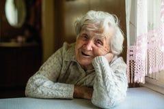 Stående av den äldre damen som sitter på tabellen fotografering för bildbyråer