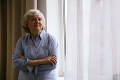 Stående av den äldre kvinnan nära fönster Utrymme för text royaltyfria bilder