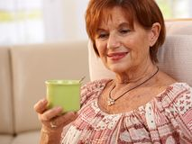Stående av den äldre kvinnan som dricker kaffe Fotografering för Bildbyråer