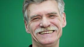 Stående av den äldre mannen som skrattar på grön bakgrund lager videofilmer