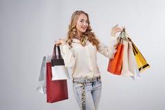 Stående av den älskvärda flickan med shoppingpåsar över vit Arkivfoto