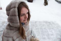 Stående av den älskvärda flickan på gatan i vintern i ett grått kort pälslag Royaltyfri Foto