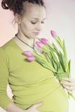 Stående av den älskvärda gravida kvinnan med tulpan Arkivfoton