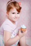Stående av den älskvärda lilla flickan med muffin Fotografering för Bildbyråer