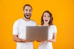 Stående av den älskvärda mannen och kvinnan som rymmer silverbärbara datorn, medan stå isolerat över gul bakgrund royaltyfria bilder