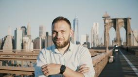 Stående av den övre gesten för lycklig europeisk manvisningtumme som ler på kameran på panorama för Brooklyn bro, New York City 4 arkivfilmer