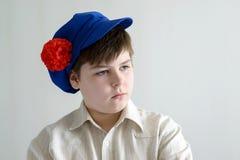 Stående av den aboy tonåringen i ryskt nationellt lock med kryddnejlikor Arkivfoto
