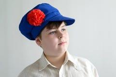 Stående av den aboy tonåringen i ryskt nationellt lock med kryddnejlikor Arkivbilder
