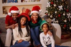 Stående av den afro amerikanska familjen i jultomtenhattar på jul fotografering för bildbyråer