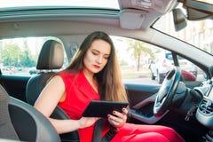 Stående av den allvarliga affärsdamen, caucasian chaufför för ung kvinna i röd sommardräktinställning - upp rutten på en navigatö royaltyfri fotografi