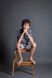 Stående av den allvarliga eftertänksamma ledsna tonåringen på stol Royaltyfria Bilder
