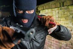 Stående av den allvarliga maskerade hållande kofoten för gangster medan pointi Royaltyfri Bild