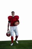 Stående av den amerikanska fotbollsspelaren som går och rymmer fotboll och hjälmen Royaltyfri Fotografi