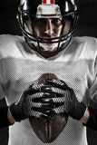 Stående av den amerikanska fotbollsspelaren som rymmer en boll royaltyfri fotografi