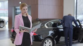 Stående av den angenäma gulliga flickan i rosa omslag med en stor bok om bilar framme av par som väljer medlet Mannen öppnar stock video