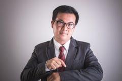 Stående av den asiatiska affärsmannen med handpunkt på hans handled Tid arkivbild