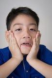 Stående av den asiatiska gulliga pojken som är ledsen och ser mycket besviken Arkivfoton