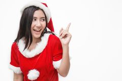 Stående av den asiatiska härliga kvinnan som bär santa custume med hennes fingerpunkt upp Fotografering för Bildbyråer