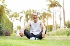 Stående av den asiatiska höga mannen som kopplar av och sitter på gräs på th Arkivfoton