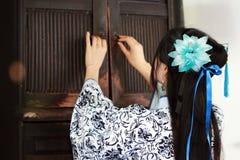 Stående av den asiatiska kinesiska flickan i den traditionella klänningen, blå och vit porslinstil Hanfu, öppet forntida skåp för Arkivbilder