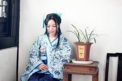 Stående av den asiatiska kinesiska flickan i den traditionella klänningen, blå och vit porslinstil Hanfu, sitta som för kläder är Arkivfoton