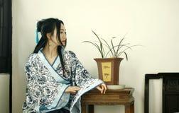 Stående av den asiatiska kinesiska flickan i den traditionella klänningen, blå och vit porslinstil Hanfu, sitta som för kläder är Fotografering för Bildbyråer