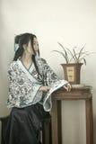 Stående av den asiatiska kinesiska flickan i den traditionella klänningen, blå och vit porslinstil Hanfu, sitta som för kläder är Royaltyfria Bilder
