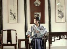 Stående av den asiatiska kinesiska flickan i den traditionella klänningen, blå och vit porslinstil Hanfu, sitta som för kläder är Royaltyfri Foto