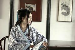 Stående av den asiatiska kinesiska flickan i den traditionella klänningen, blå och vit porslinstil Hanfu, sitta som för kläder är Arkivbilder