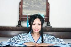 Stående av den asiatiska kinesiska flickan i den traditionella klänningen, blå och vit porslinstil Hanfu, sitta som för kläder är Arkivfoto